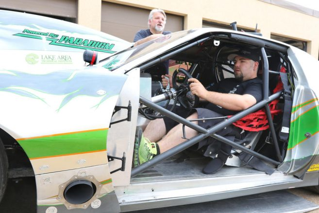 Driver Greg Schmidt sits in his car while his dad and crew chief Al Schmidt talks Wednesday at Paradigm Automotive in Brainerd. (Kelly Humphrey, Brainerd Dispatch - Gallery)