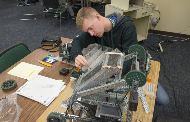 Student in the final stages of his robotics project.