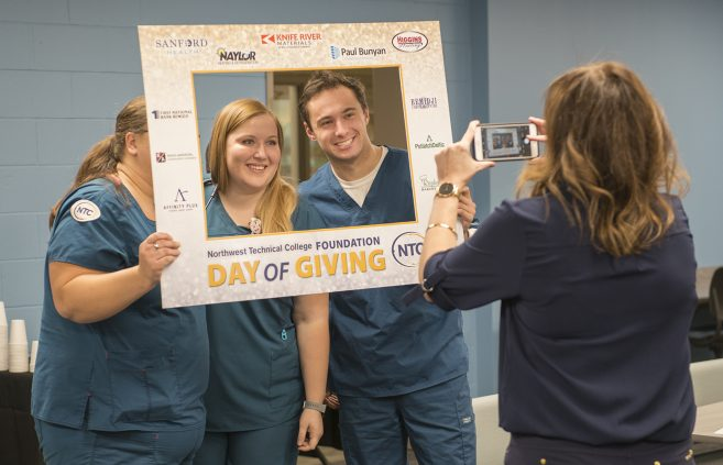 NTC students pose with a NTC Day of Giving frame.