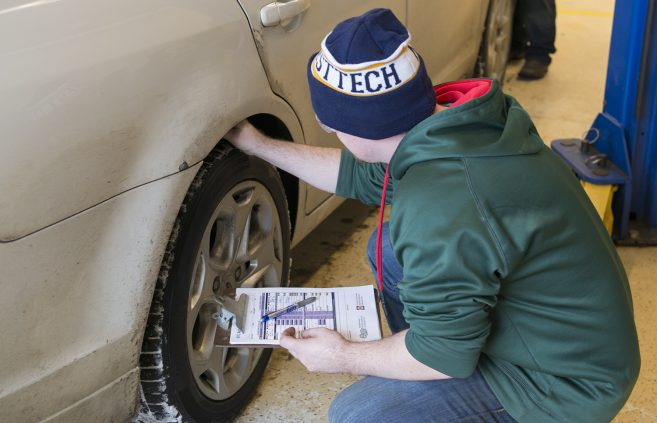 An NTC student examines a vehicle during the car winterization clinic.