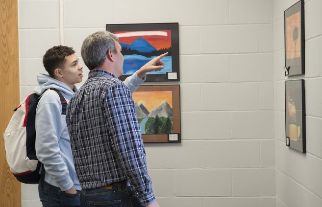 Student from Cass-Lake & Darrin Strosahl observing the artwork.