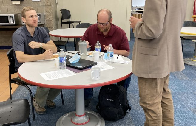 3 NTC employees talk around a table at Admin Day