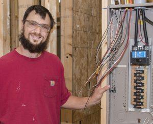 Shawn Graupmann standing next to an electrical box